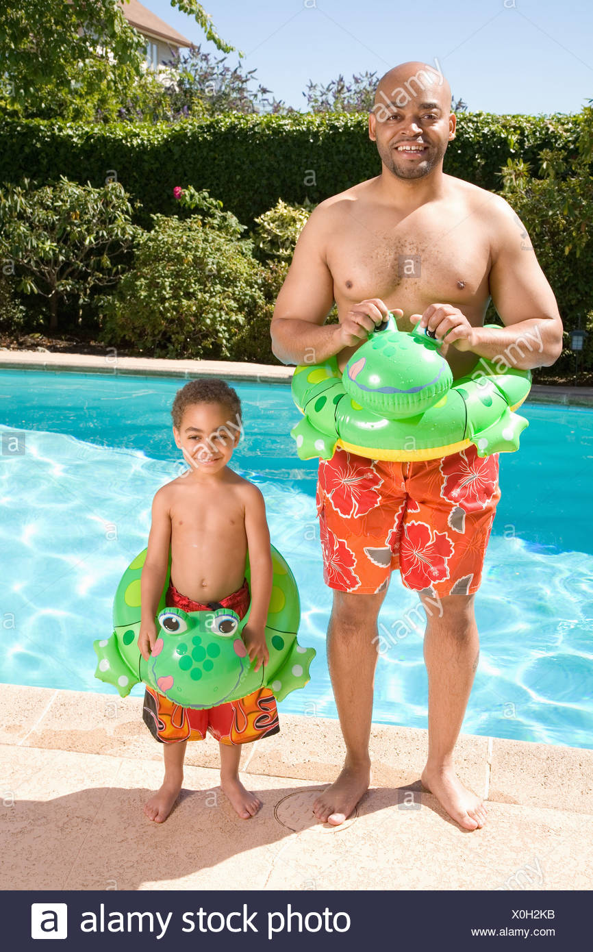 Father and son wearing identical flotation devices by pool Stock Photo