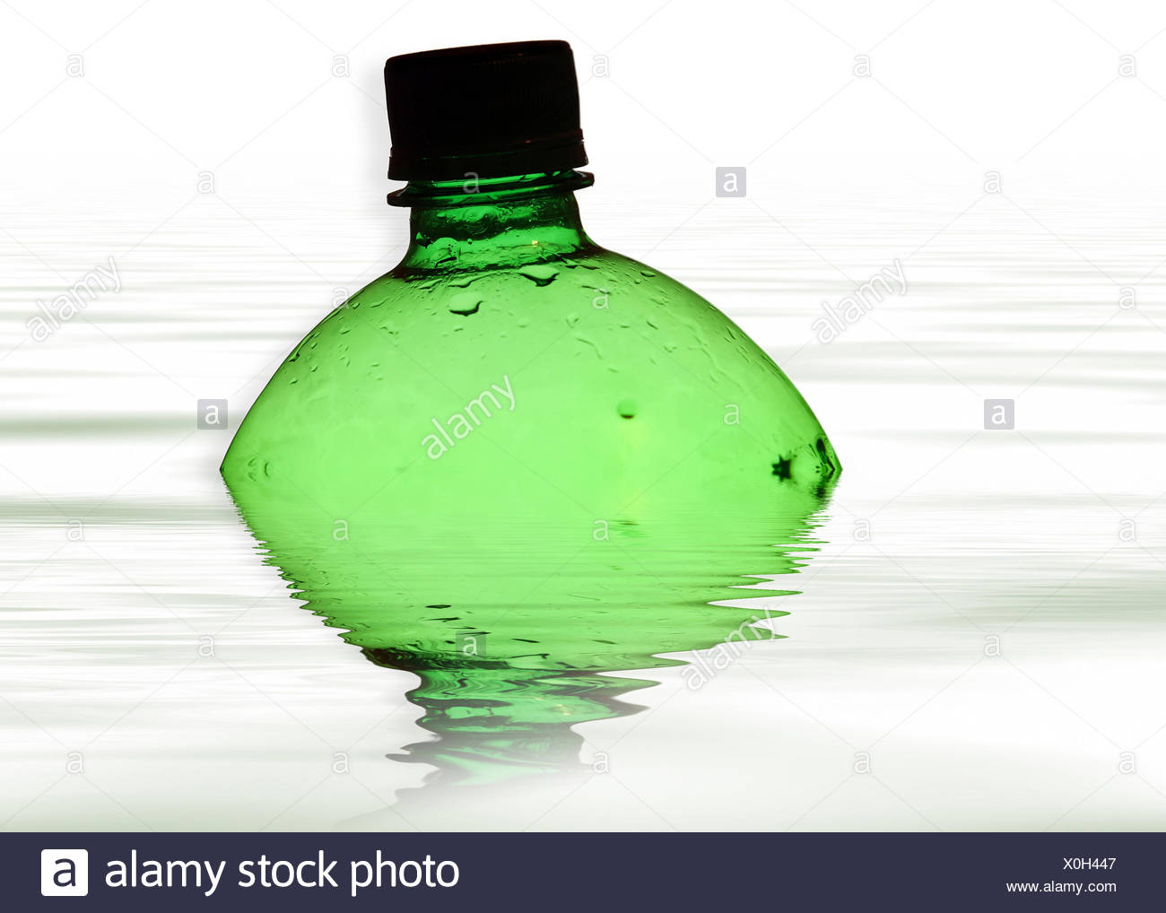 Green bottle floating in water - Stock Image