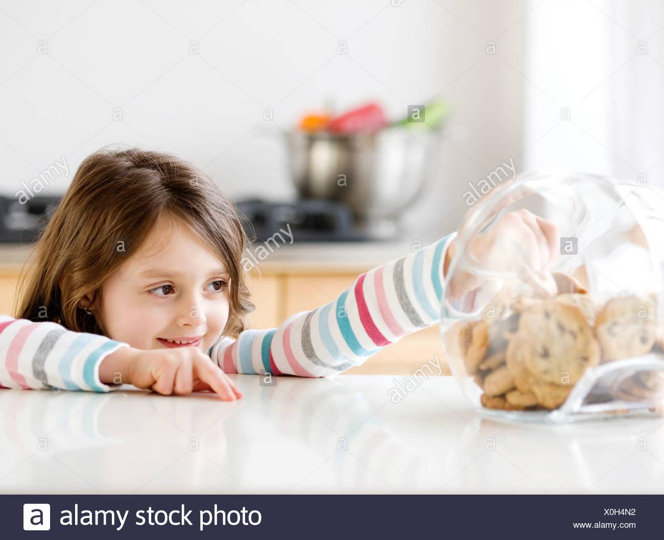 Girl reaching into cookie jar - Stock Image