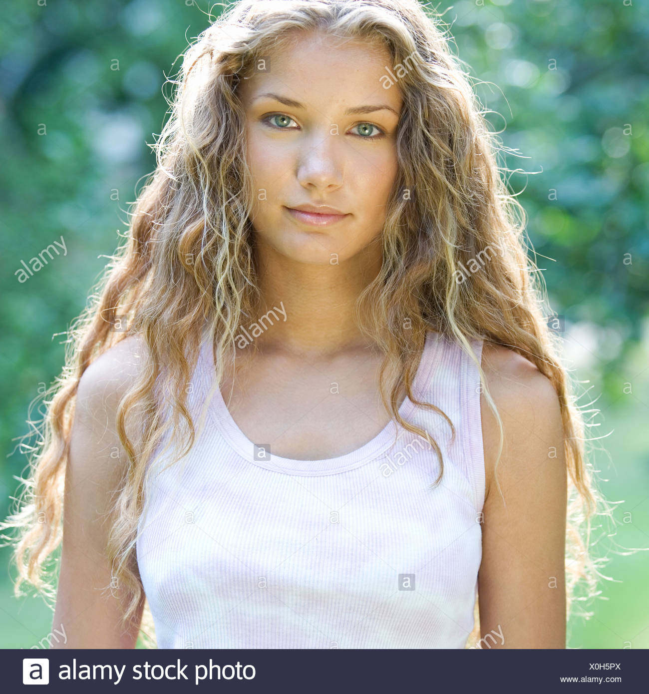 Portrait of a teenage girl stranding in a park - Stock Image
