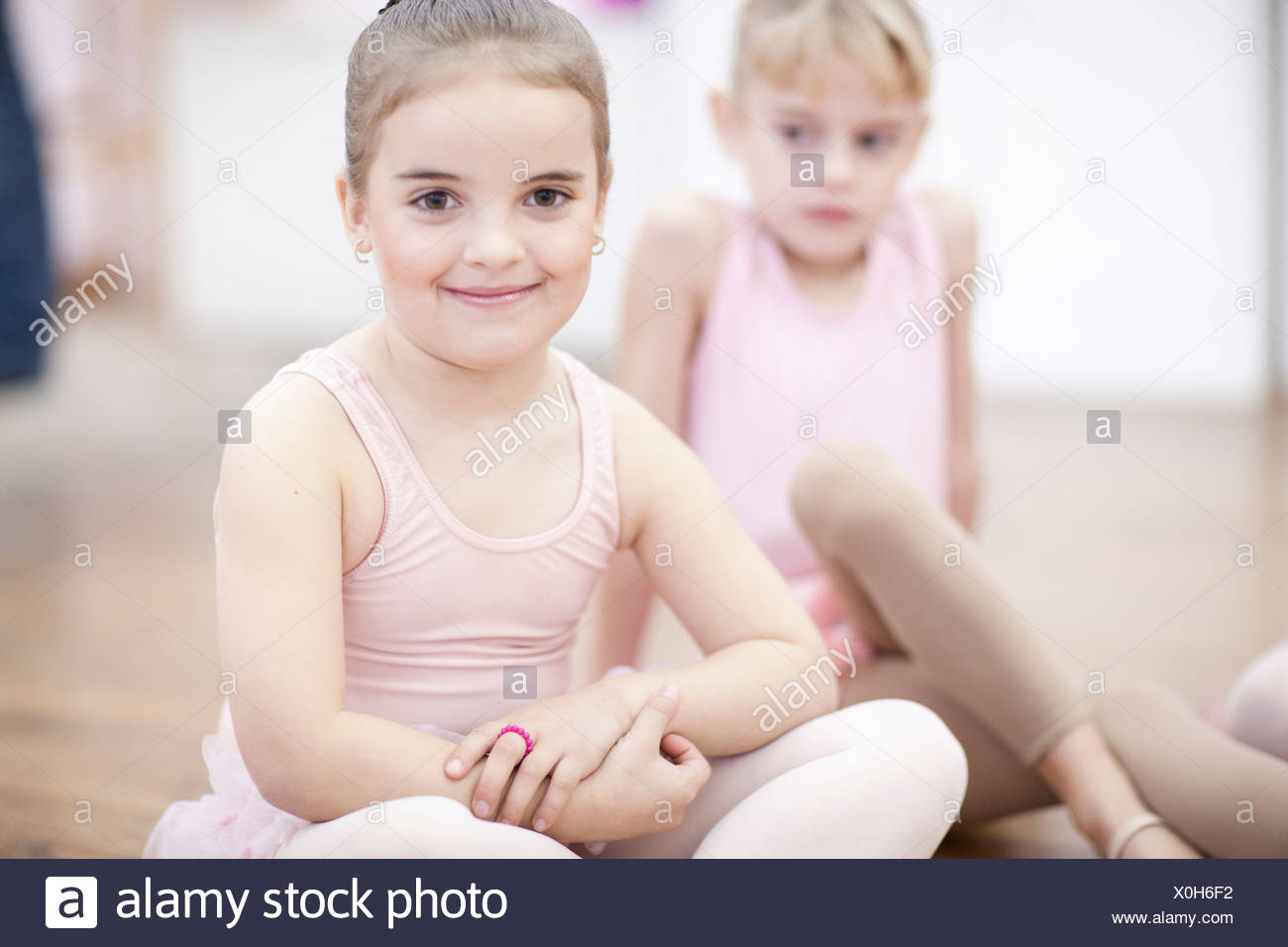 Two young ballerinas sitting on floor - Stock Image