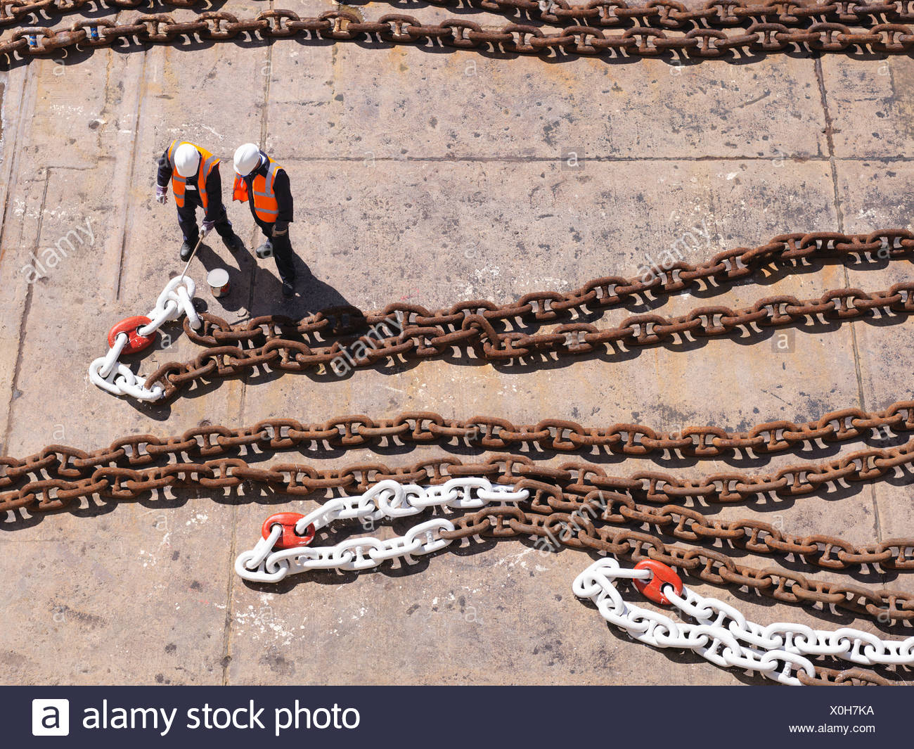 Aerial view of workers examining chain - Stock Image