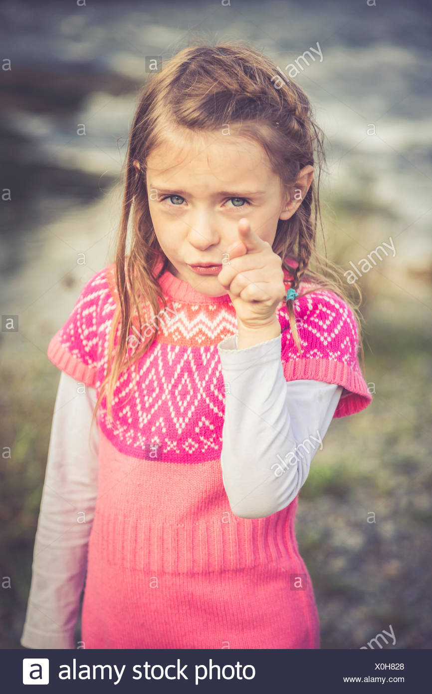 Portrait of little girl pointing at viewer - Stock Image