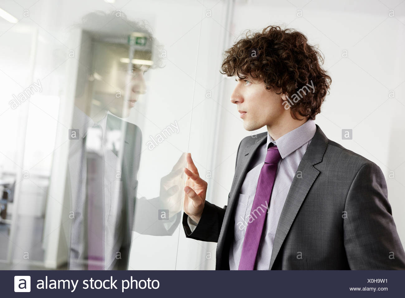 Businessman looking through glass wall, with reflection - Stock Image