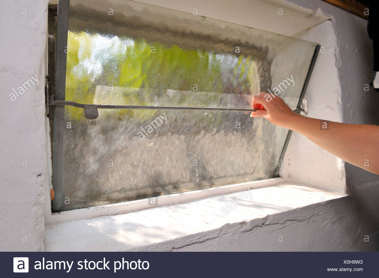 Woman opening a basement window to let some air in - Stock Image