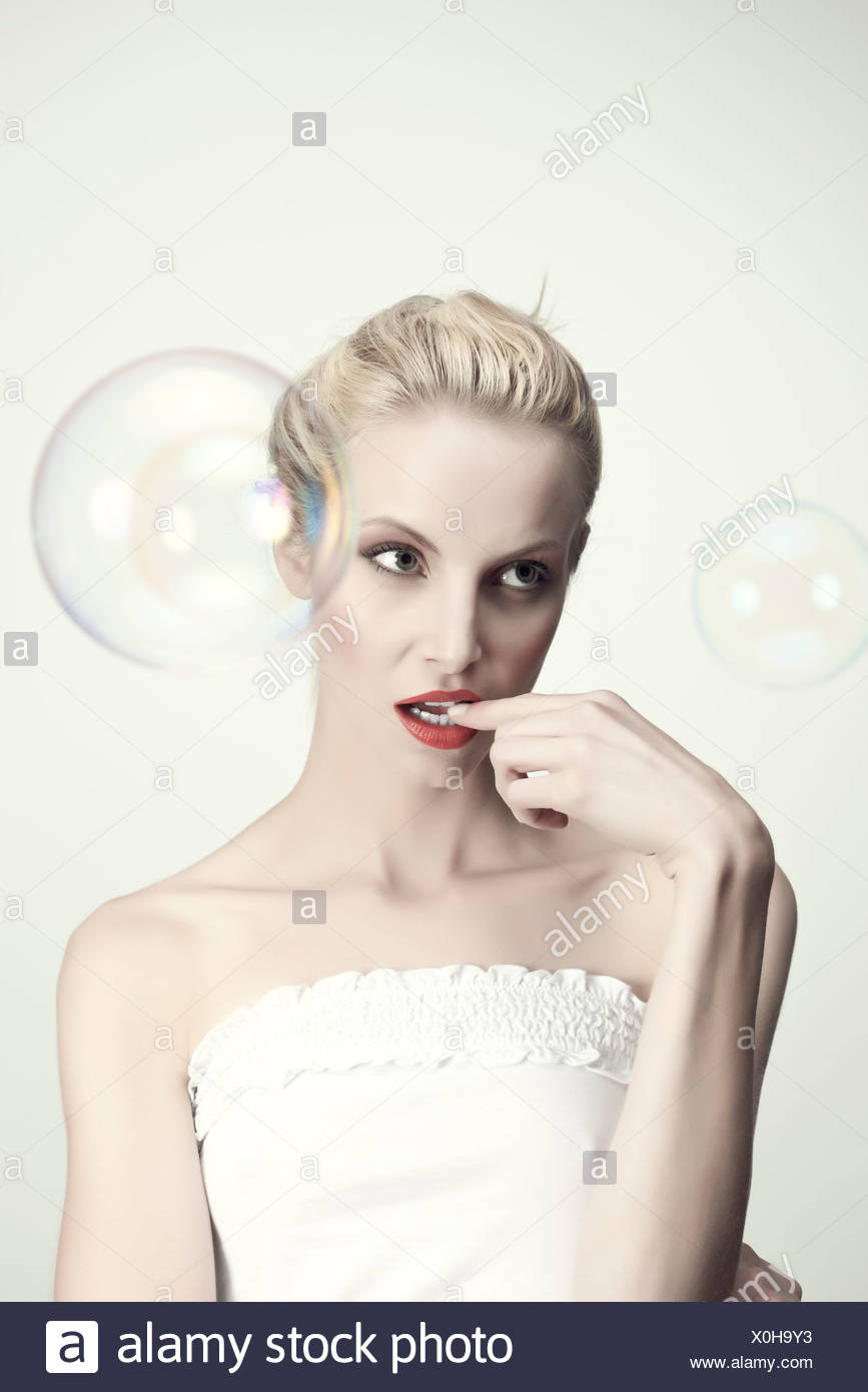 Young woman biting finger, portrait - Stock Image