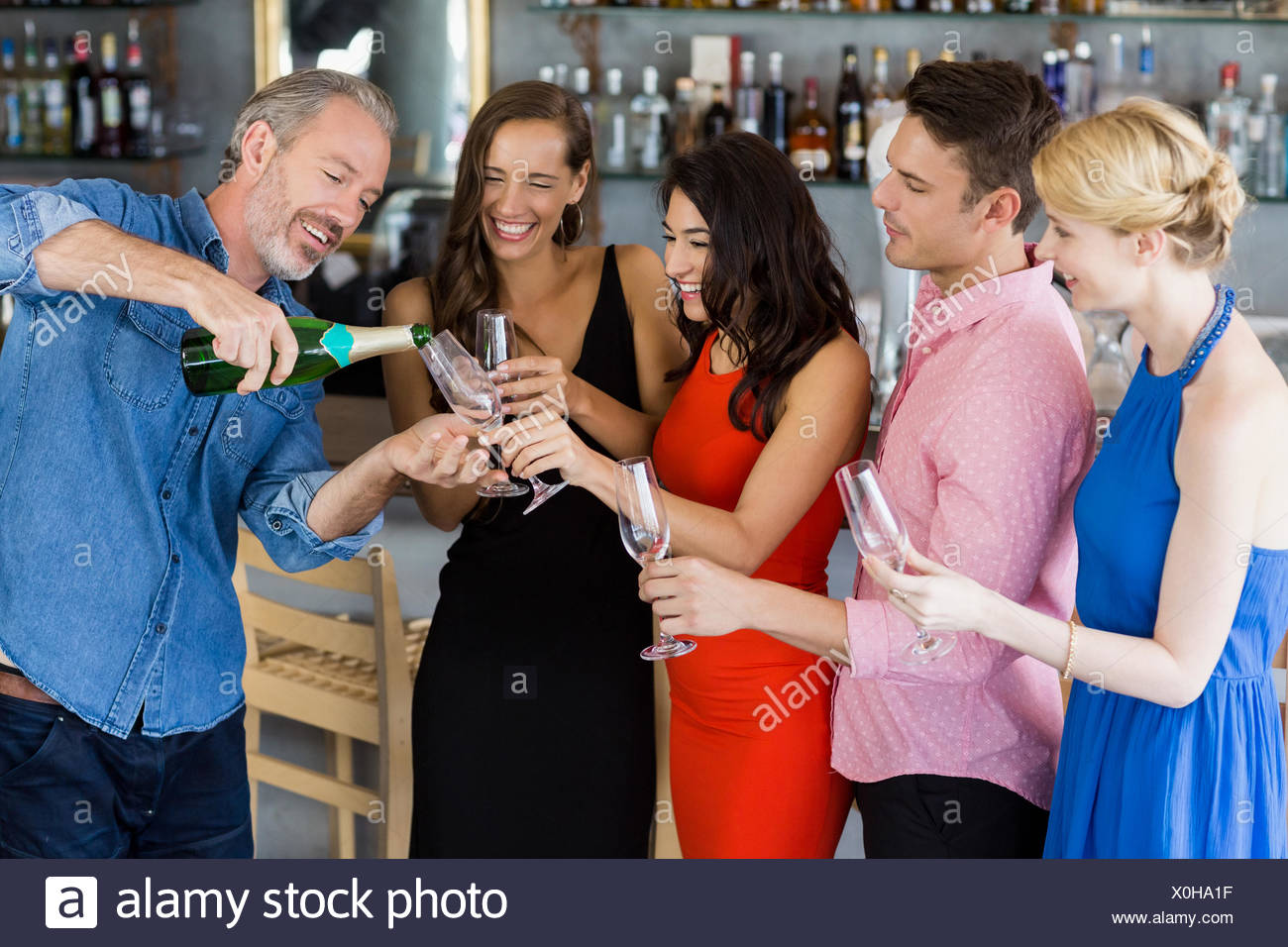 Man pouring champagne into glass - Stock Image