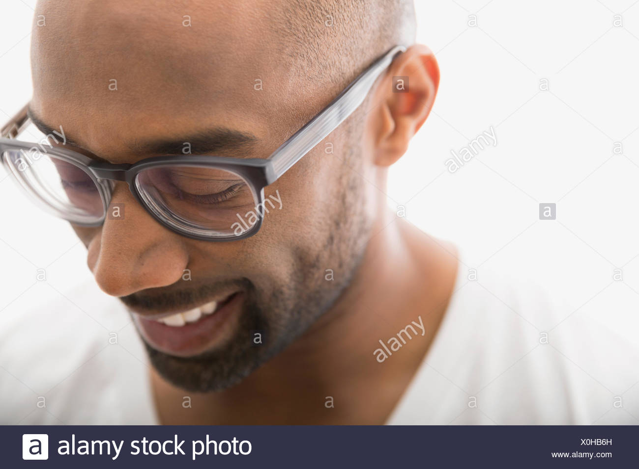 Close up of man in eyeglasses looking down - Stock Image