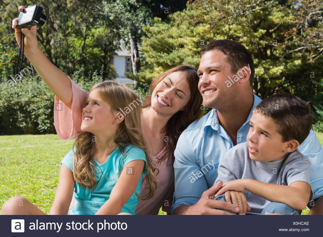 Happy family in a park taking photos - Stock Image