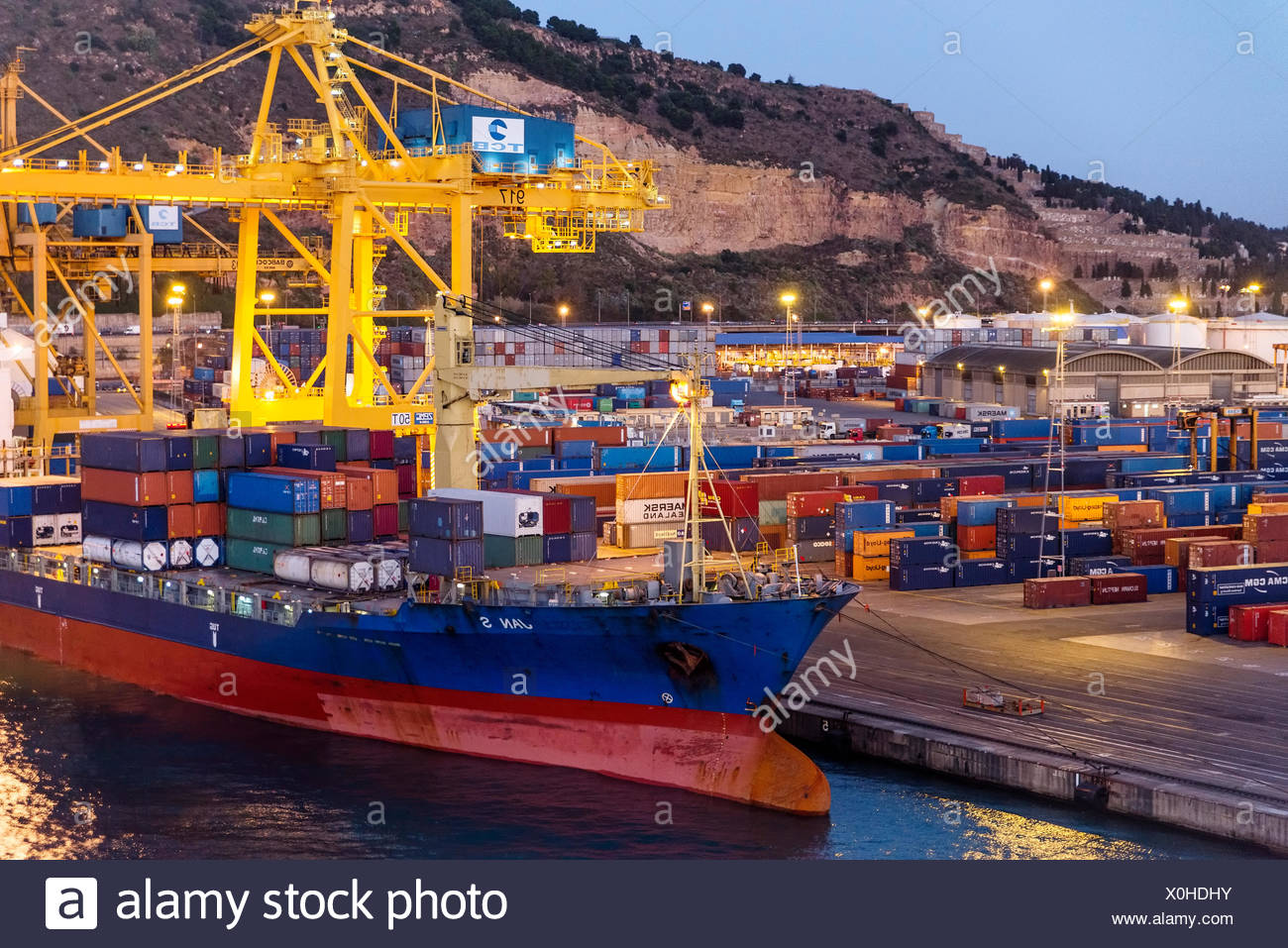 Cargo containers being loaded on to a shipping freighter , Barcelona, Spain - Stock Image