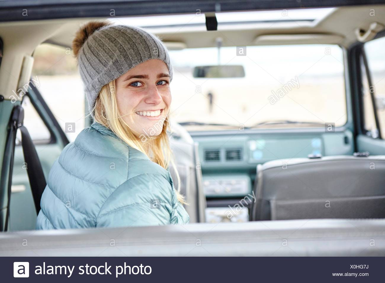 Portrait of young woman in car at beach wearing knit hat - Stock Image