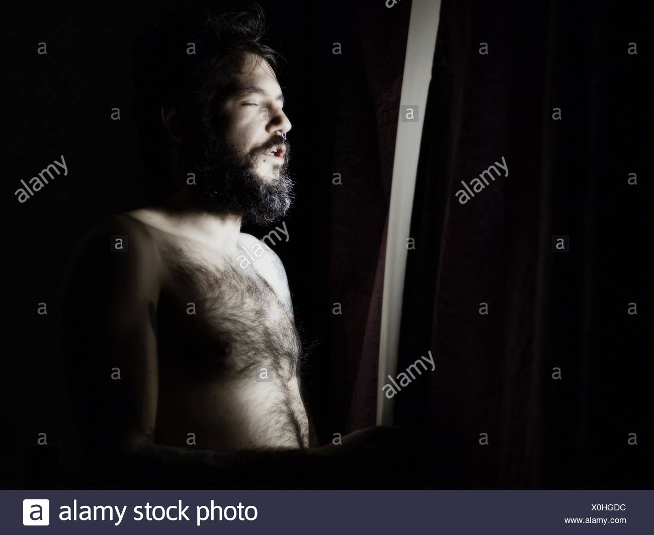 Man Standing At Window With Eyes Closed - Stock Image