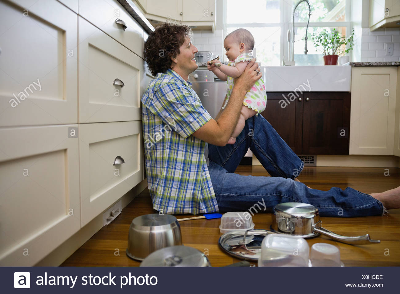 Profile shot of father and baby girl in kitchen - Stock Image