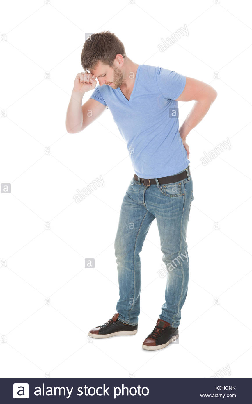 Full length of mid adult man suffering from backache over white background - Stock Image