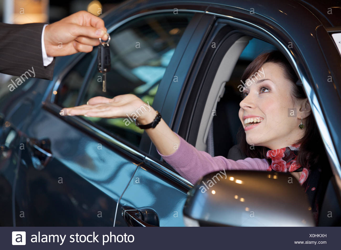 Young woman receiving the car keys from car salesman - Stock Image