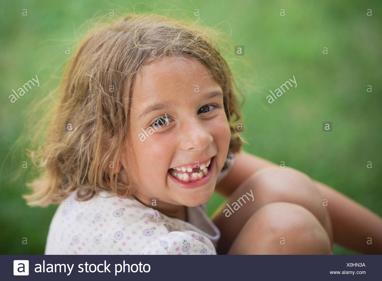 Girl (4-5) smiling with missing tooth - Stock Image