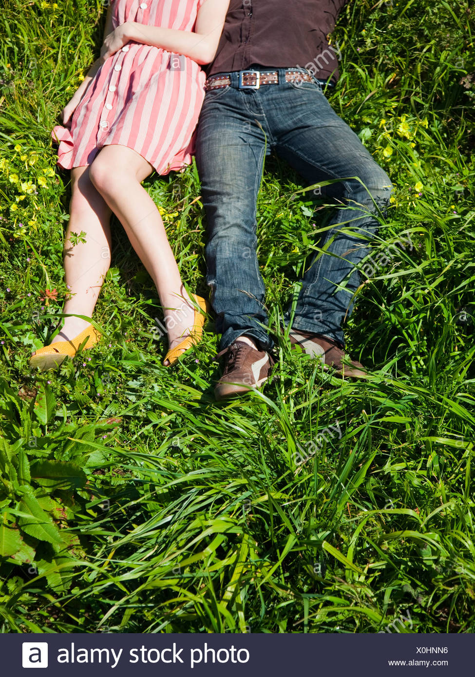 USA, San Francisco, California, young couple lying on grass, low section - Stock Image