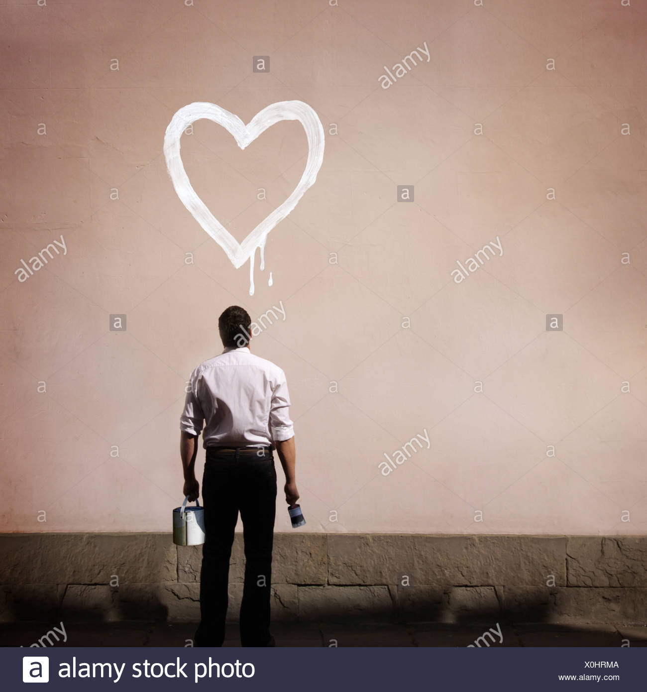 man with heart painted on wall - Stock Image