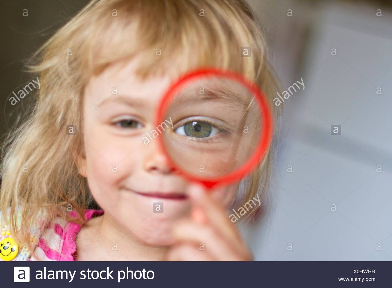 Blond girl looking through lupe - Stock Image