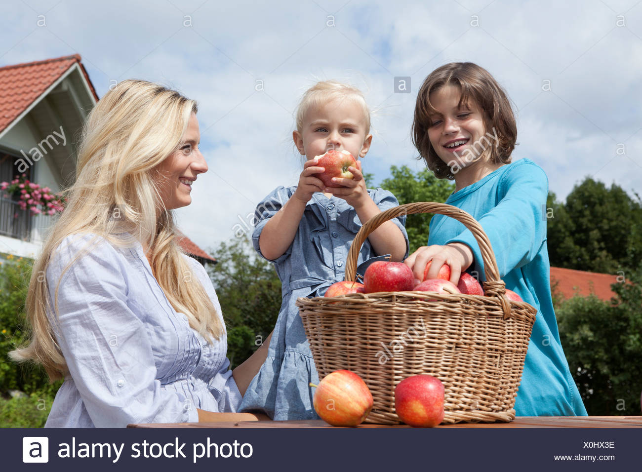 Germany, Munich, Mother with children eating apples from basket - Stock Image
