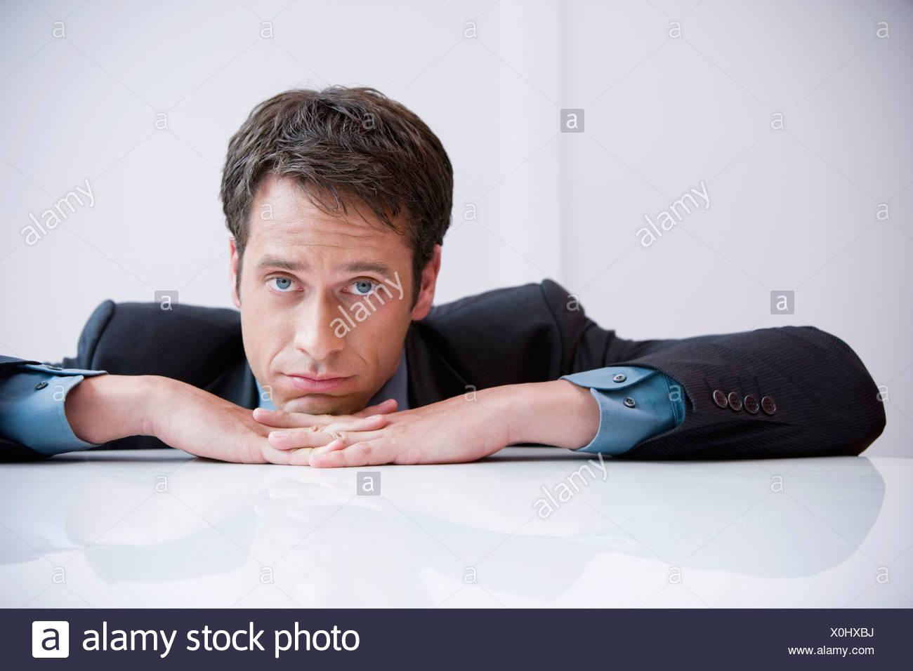 portrait of sad businessman sitting at table - Stock Image