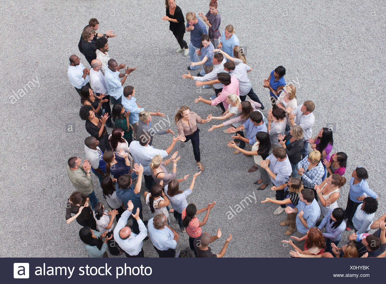 Woman walking past crowd, high-fiving people - Stock Image