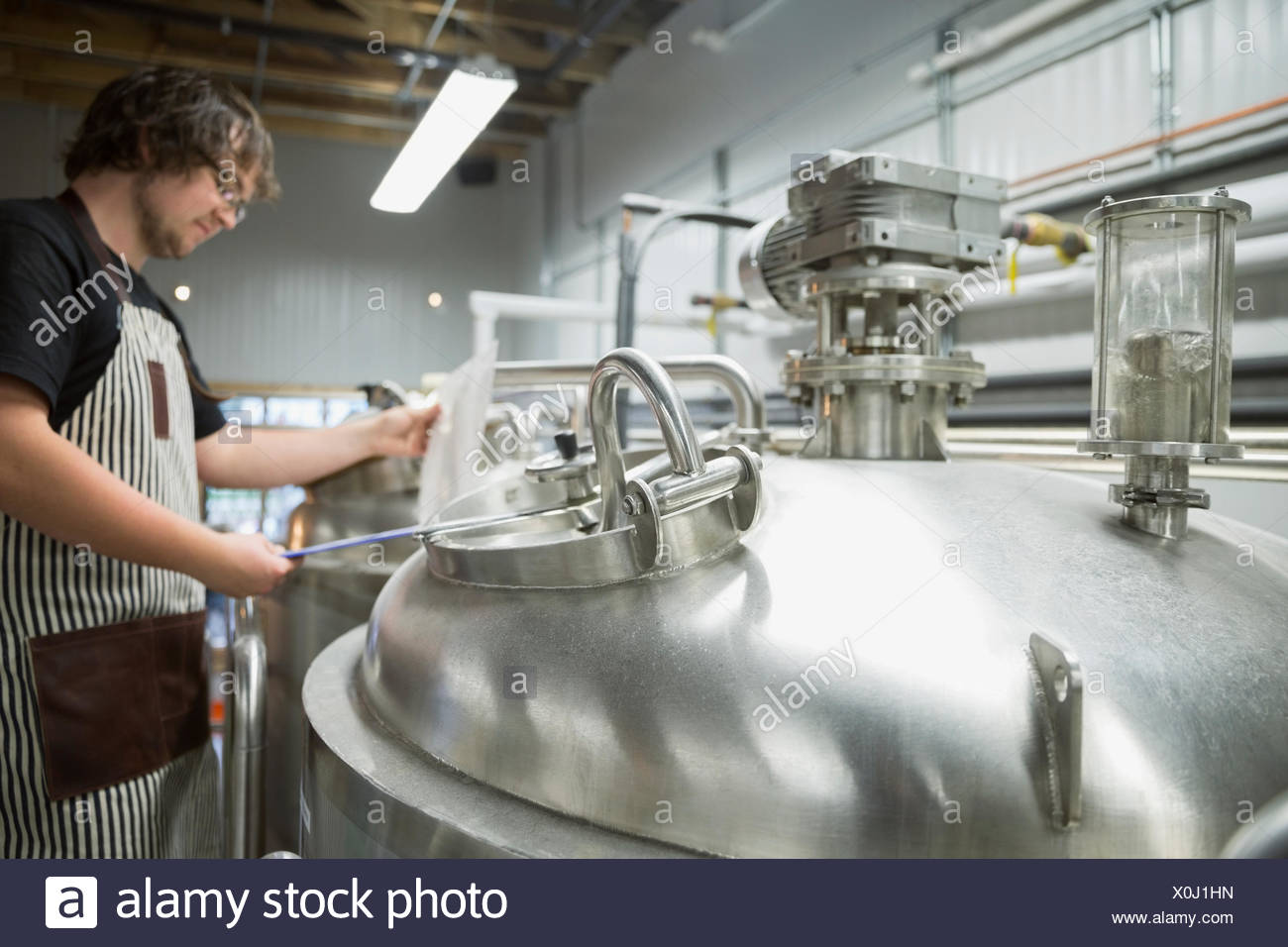 Worker with clipboard at fermentation tank in distillery - Stock Image