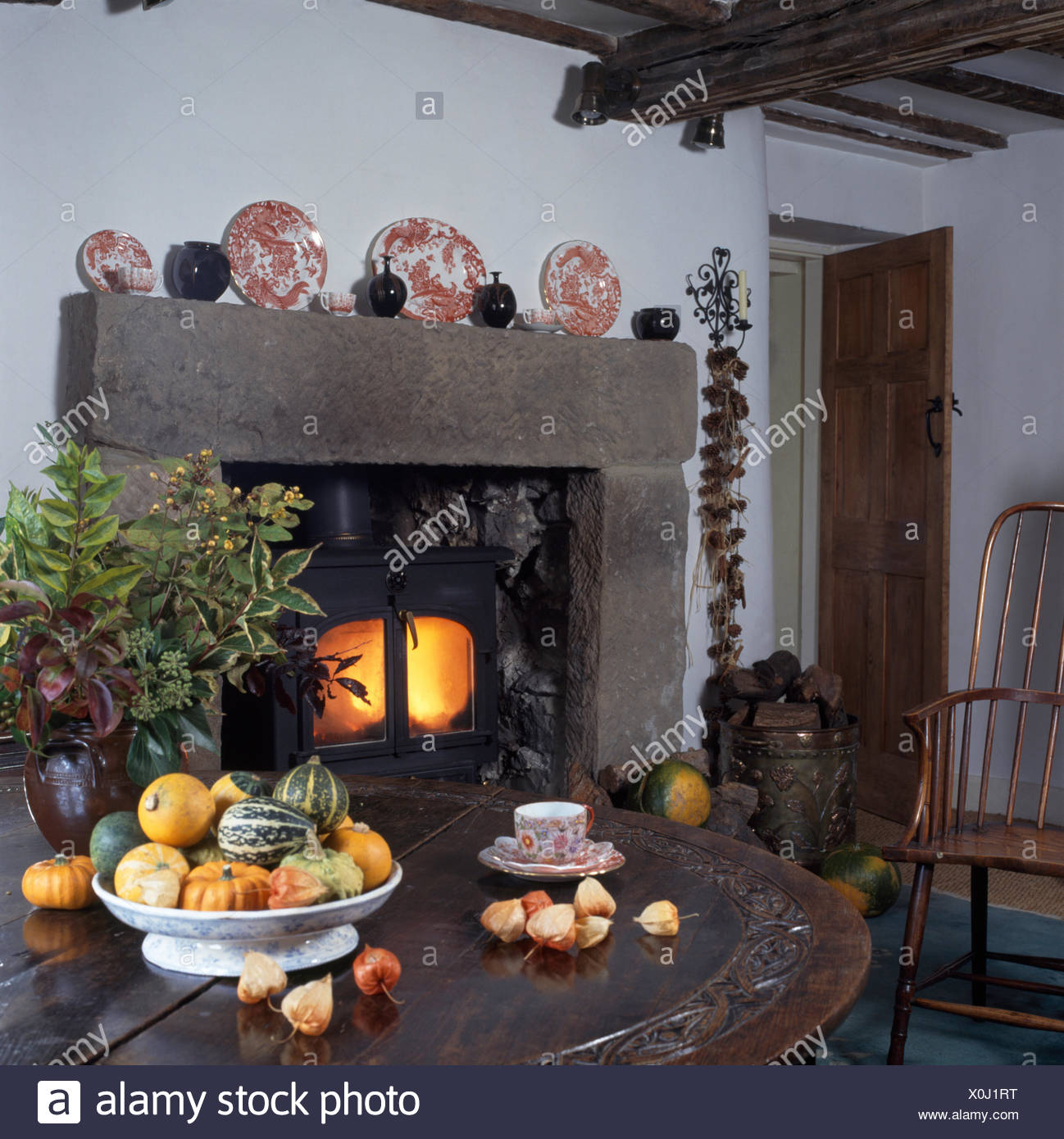 Bowl of gourds on table in country dining room with a wood burning stove in stone fireplace Stock Photo