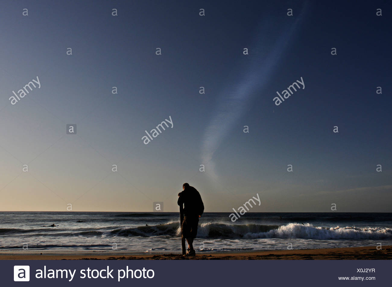 A man standing next to the sea, leaning on a wooden post - Stock Image