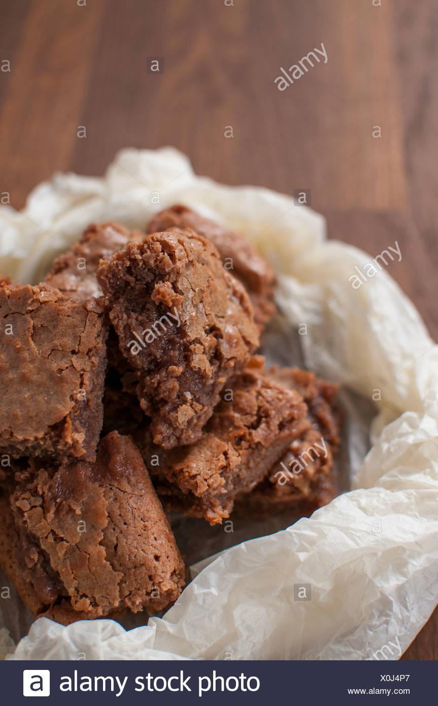 Chocolate brownies in wax paper - Stock Image