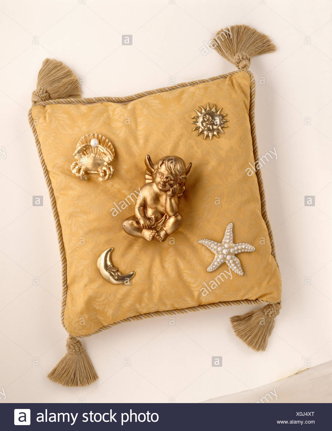 Gold cherub on gold tasseled cushion with attached astronomy motifs - Stock Image