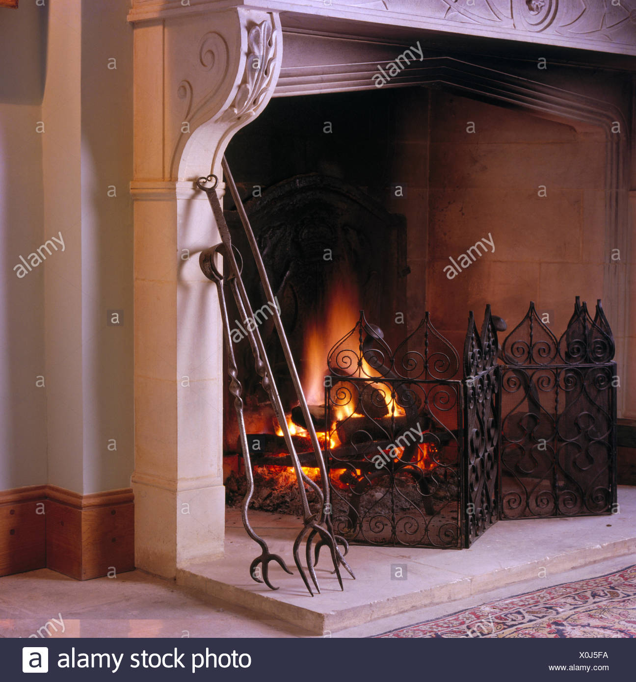 Close-up of fireplace with lighted fire and wrought iron fireguard and fire tongs - Stock Image