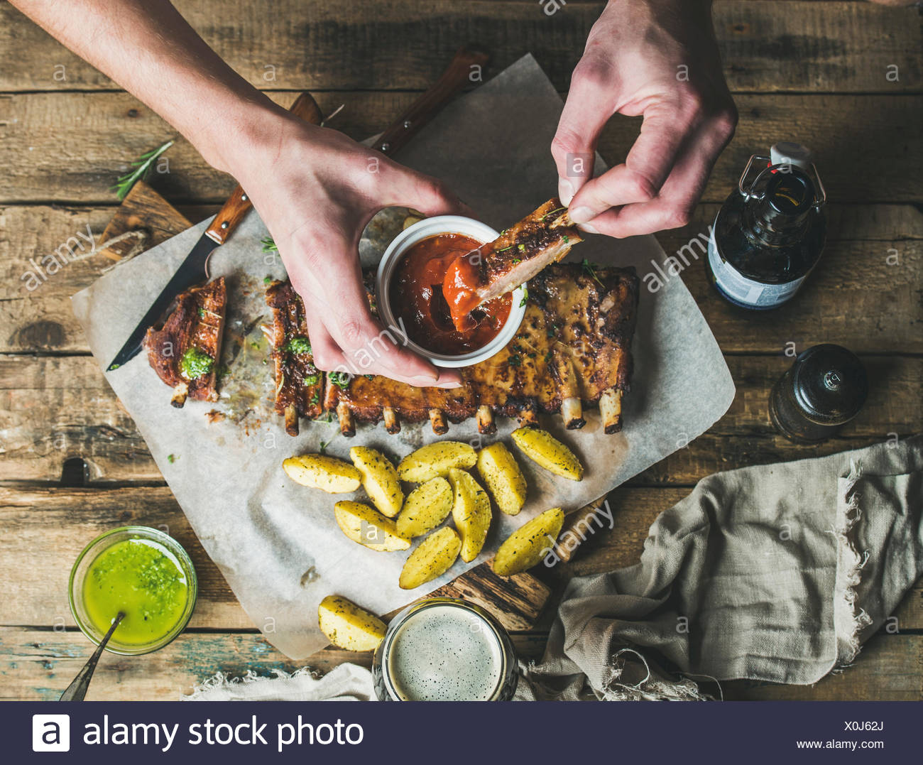 Man eating roasted pork ribs with potato pieces, garlic, rosemary and green herb sauce on rustic wooden table. Man' s hands dipp - Stock Image