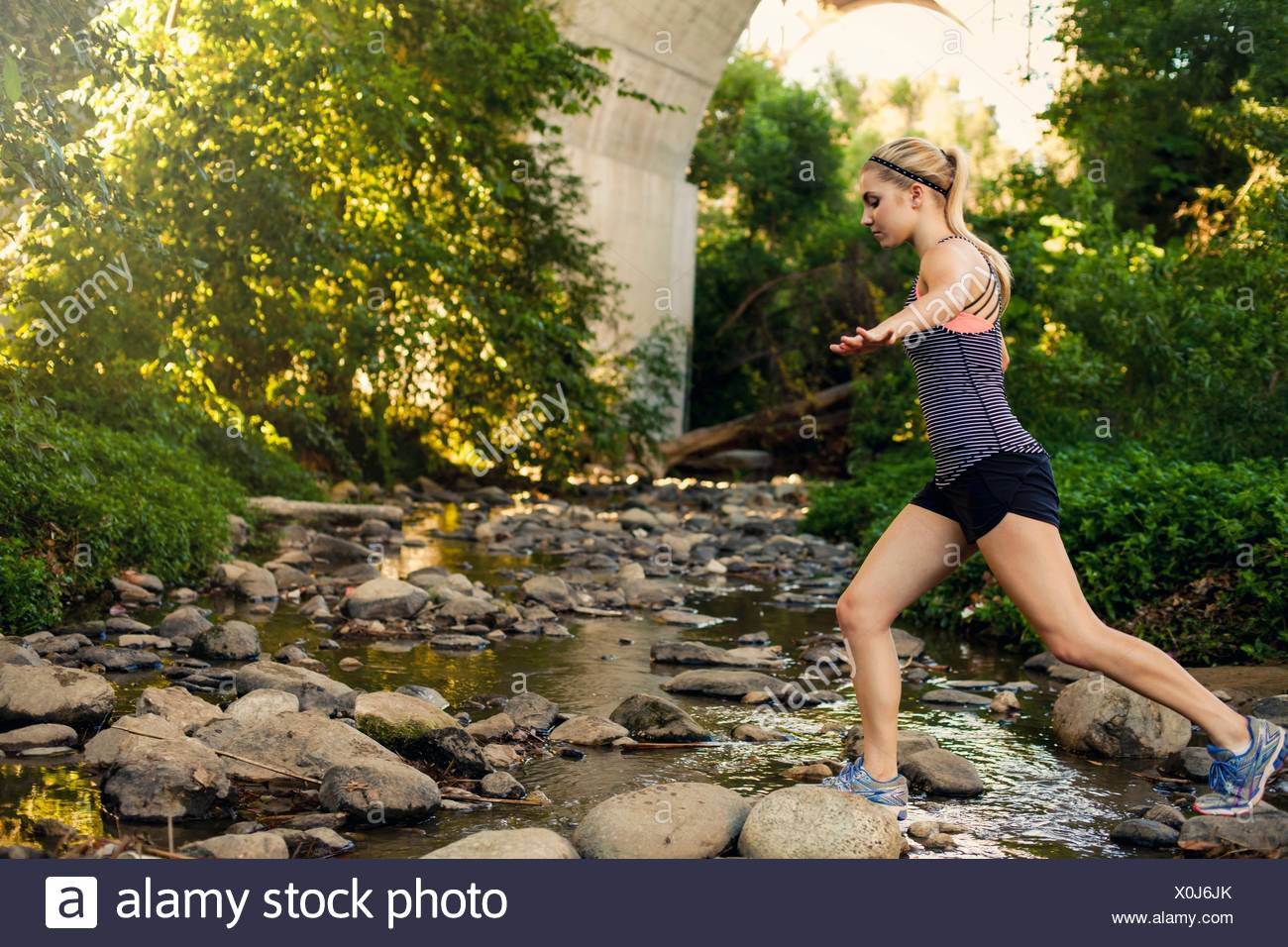 Jogger crossing stream under arch bridge, Arroyo Seco Park, Pasadena, California, USA - Stock Image