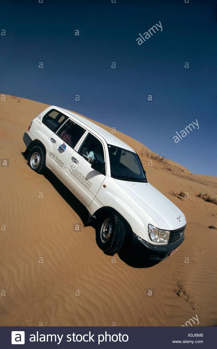 Toyota Land Cruiser, sport utility vehicle, SUV, driving down a sand dune, Wahiba Sands, Oman, Arabian Peninsula, Middle East - Stock Image