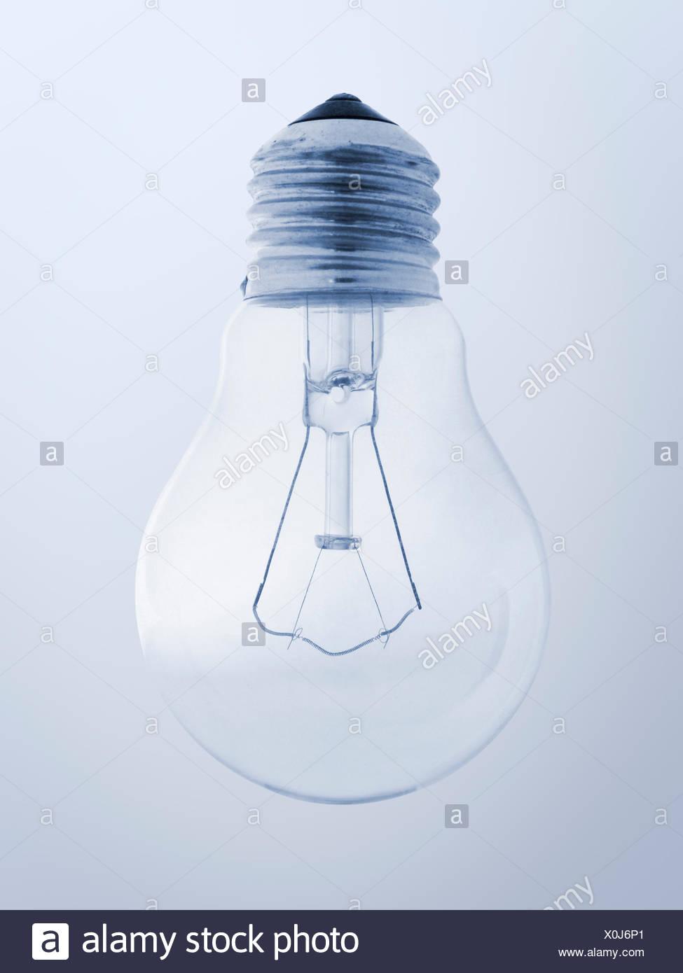 Nahaufnahme einer einzelnen glasklaren Haushalts-Glühbirne mit Schraubgewinde auf hell-blauen Verlaufs-Hintergrund Stock Photo