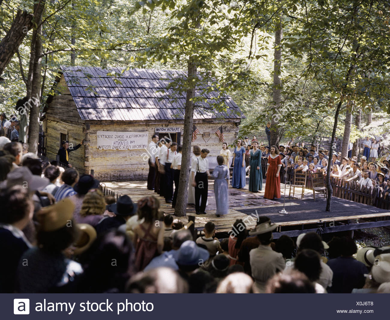Visitors crowd around the stage for a show at a folk music festival. - Stock Image