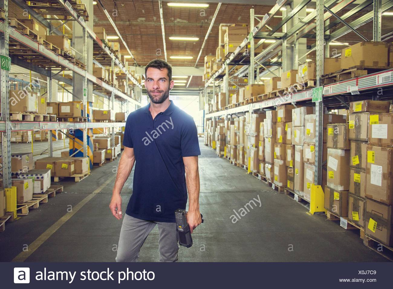 Portrait of male warehouse worker standing in distribution warehouse aisle - Stock Image