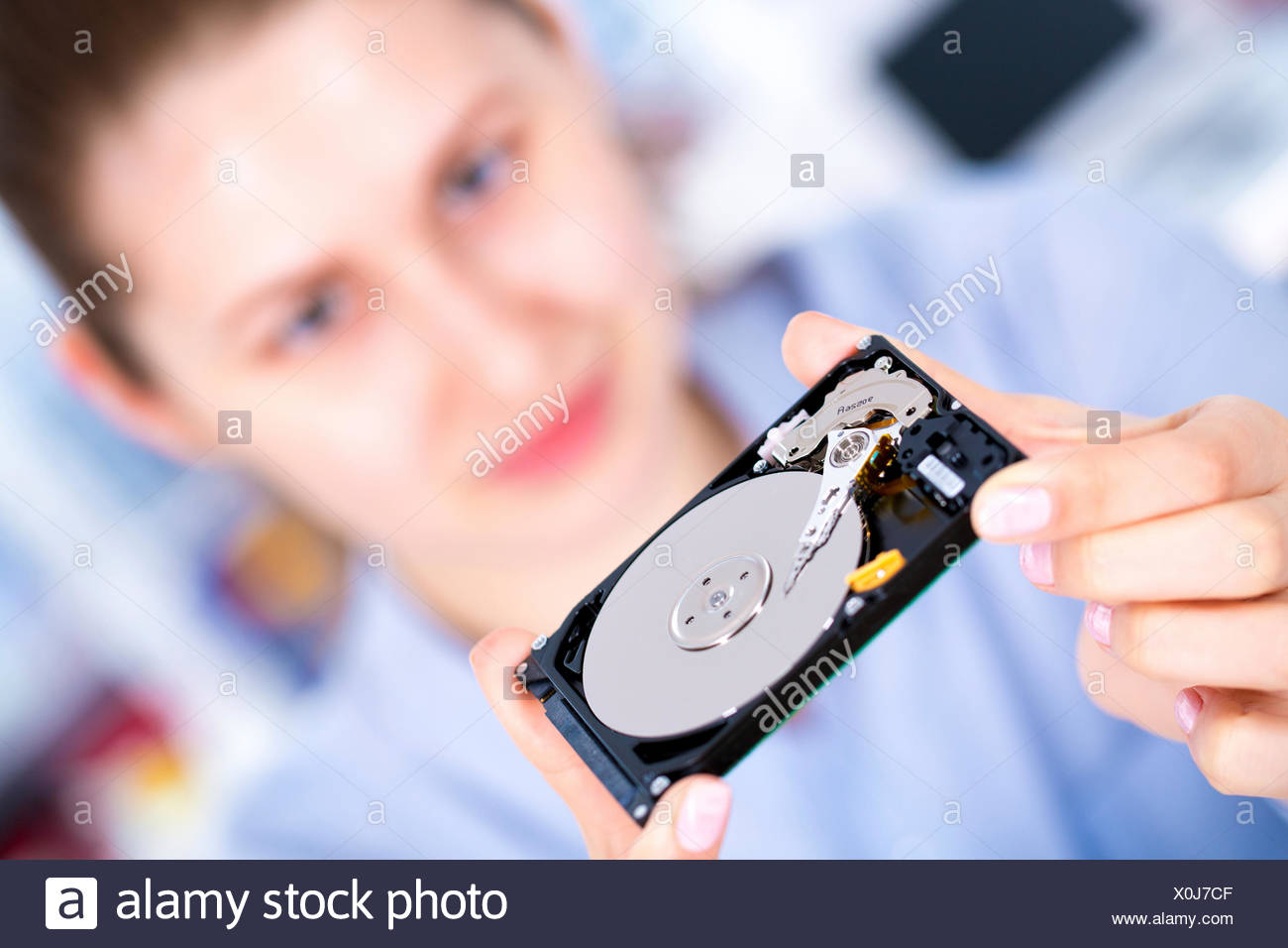 Female engineer holding hard disc drive. - Stock Image