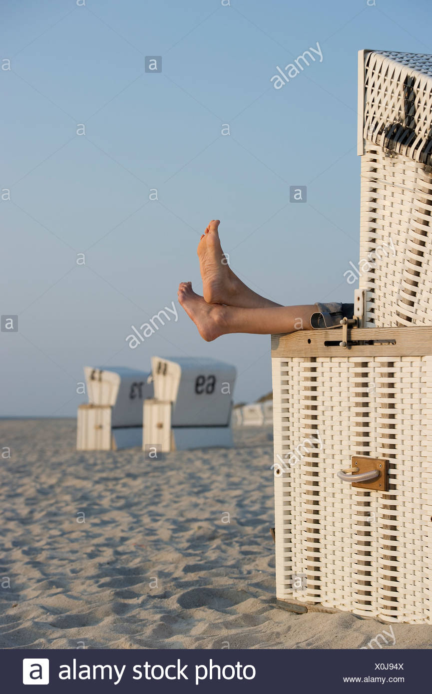 Roofed wicker beach chair and bare feet, Westerland, Sylt island, Schleswig-Holstein, Germany, Europe Stock Photo