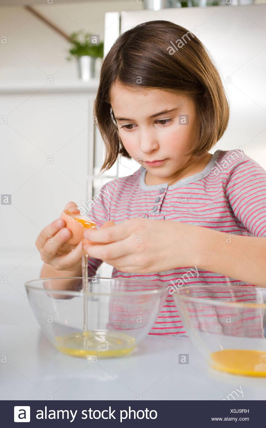 Girl separating egg yolk and egg white - Stock Image