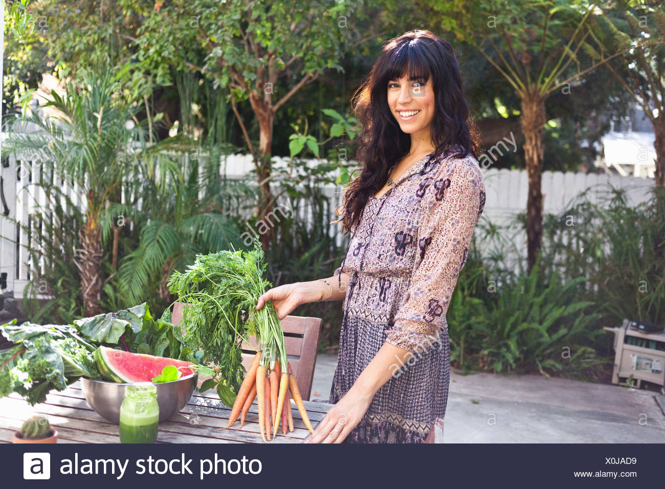 Portrait of young woman holding carrots - Stock Image