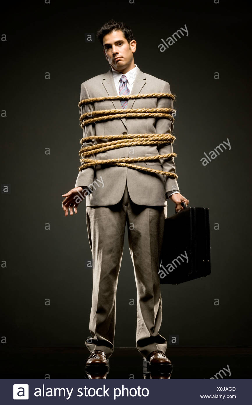 businessman in a full suit tied up with a rope around his mid section - Stock Image