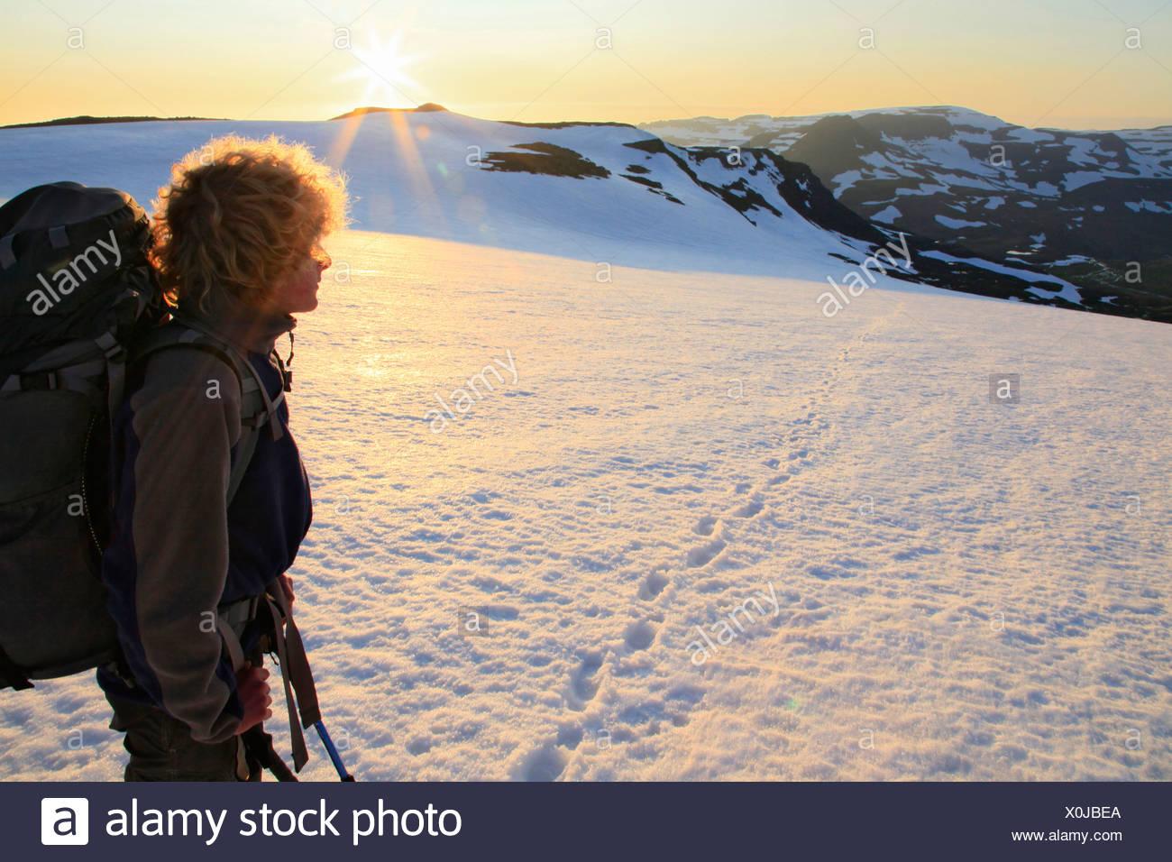 Backpacker looking back at sunrise while crossing Drangajökull ice cap, Hornstrandir Peninsula, Iceland - Stock Image