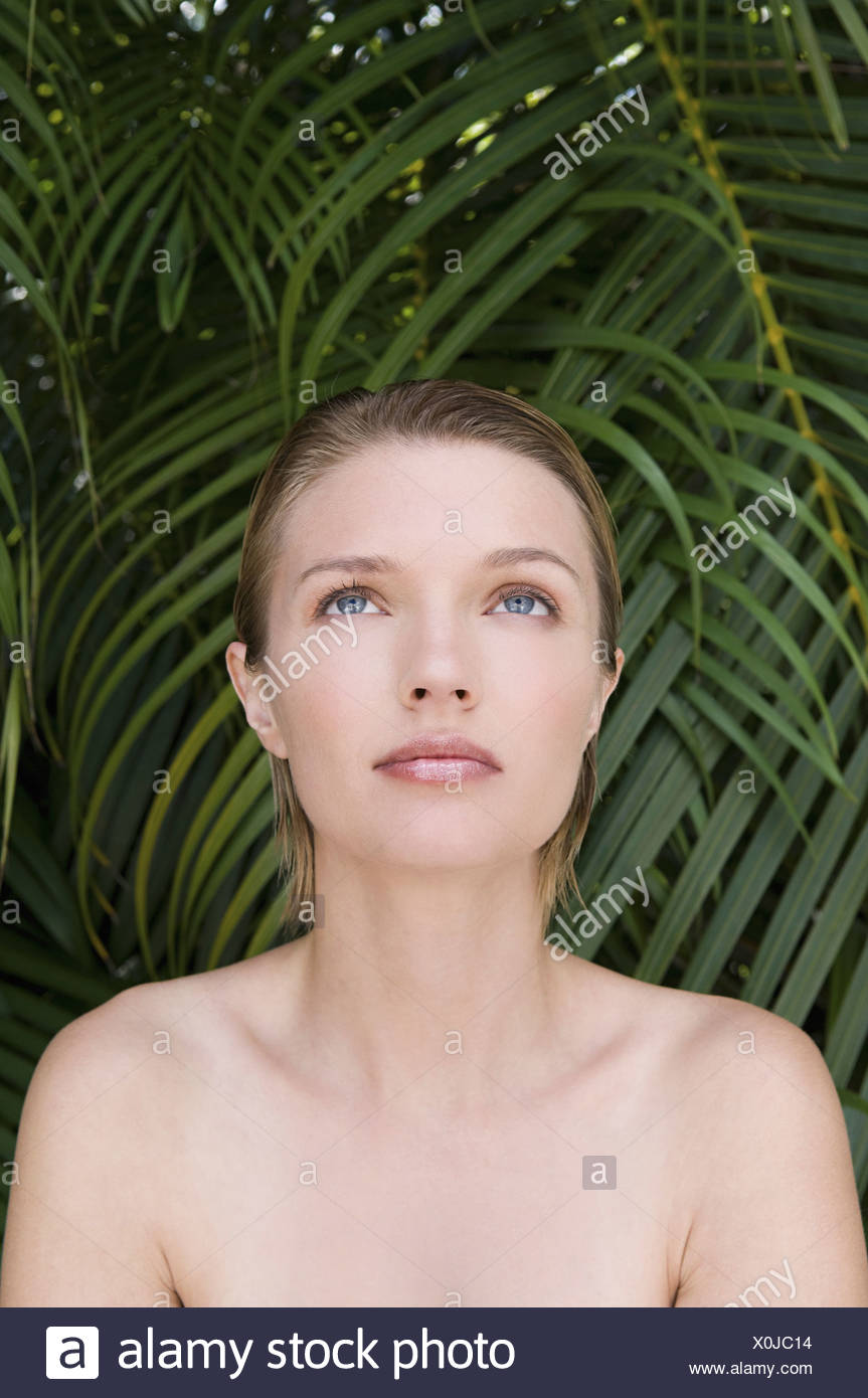 A young woman with bare shoulders looking upwards Tropical plants in the background England - Stock Image