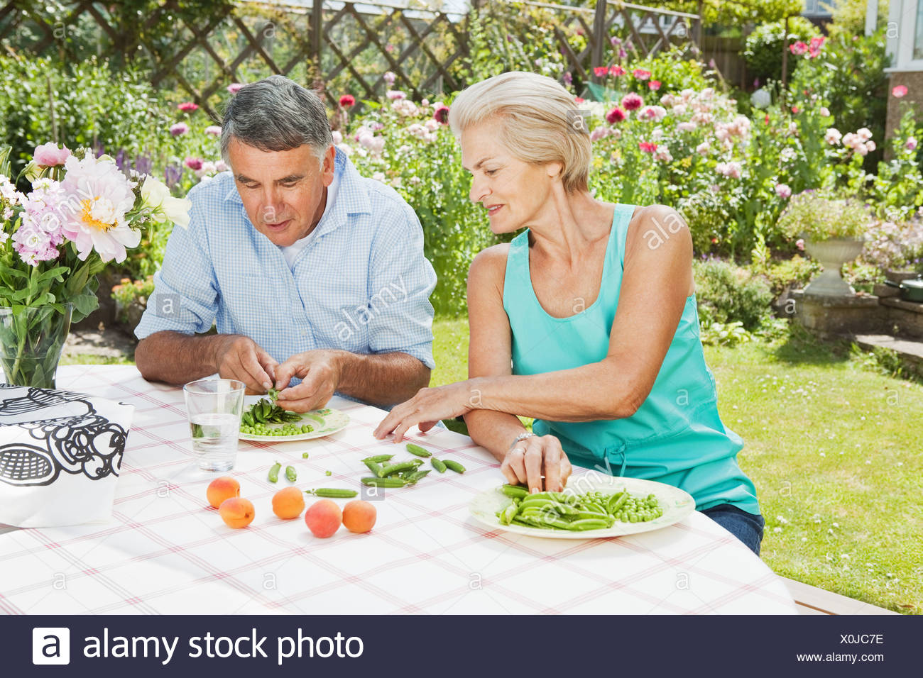 mature woman teaches partner to peel pod - Stock Image