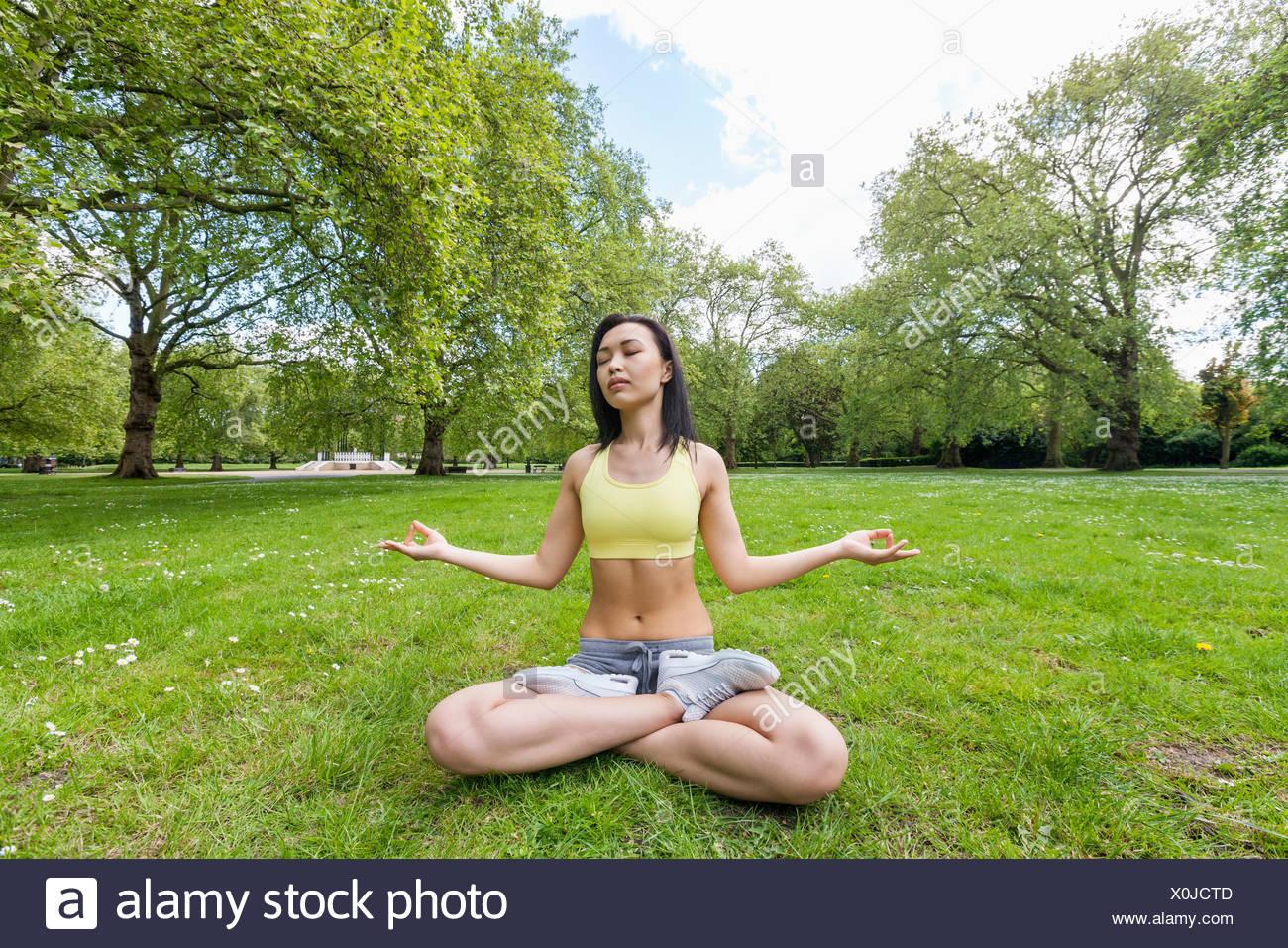 Full length of beautiful fit woman performing yoga at park - Stock Image