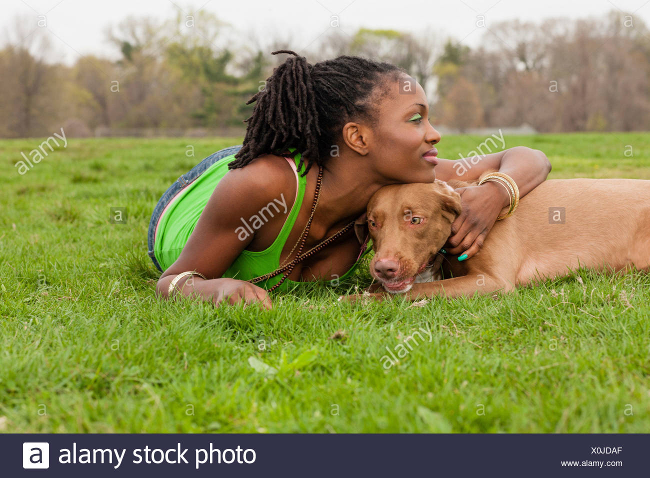 Young woman and her dog lying on grass - Stock Image