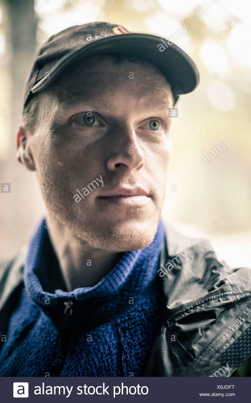 Thoughtful man wearing cap looking away outdoors - Stock Image