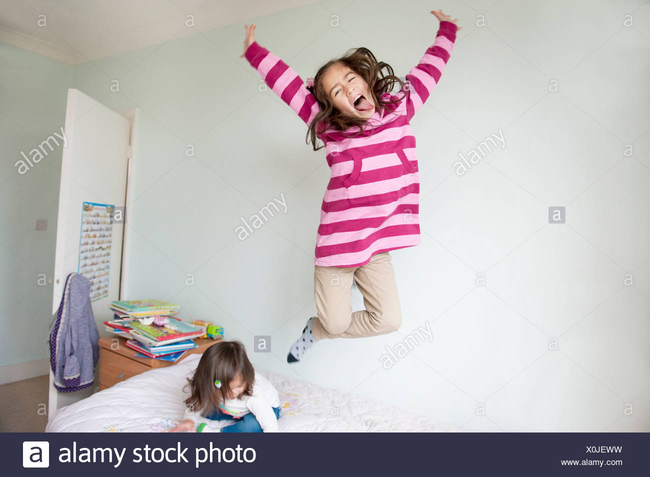 Girl jumping on bed and pulling face Stock Photo